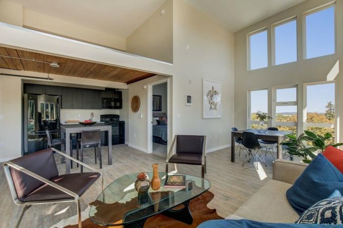 coin cuisine dans un studio blanc, table en verre asymétrique, grandes fenêtres du plafond au sol, chaise en métal et cuir