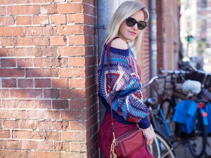 pull multicolore, petit sac à main original, jupe couleur bordeaux, lunettes de soleil, mur en briques