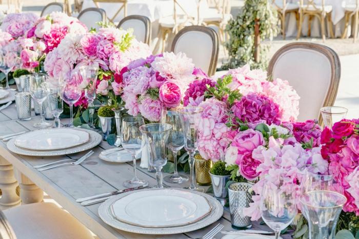 table en bois, assiettes blanches, chemin de table roses et pivoines couleur rose, chaises vintage