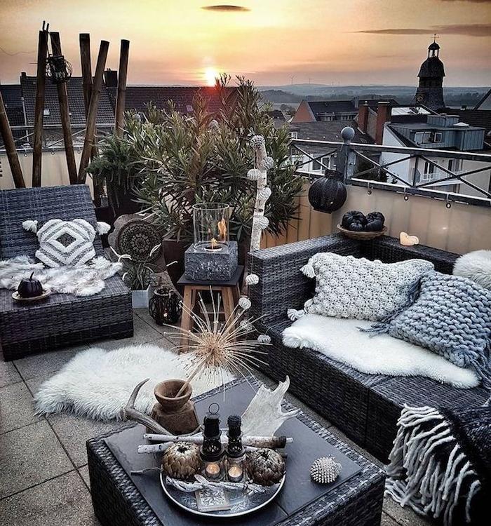 aménager son balcon style boheme chic cosy et hygge, canapé, table et fauteuil tressé, coussins décoratifs moelleux, revetement de balcon en dalles de beton, plantes exotiques, ambiance depaysante