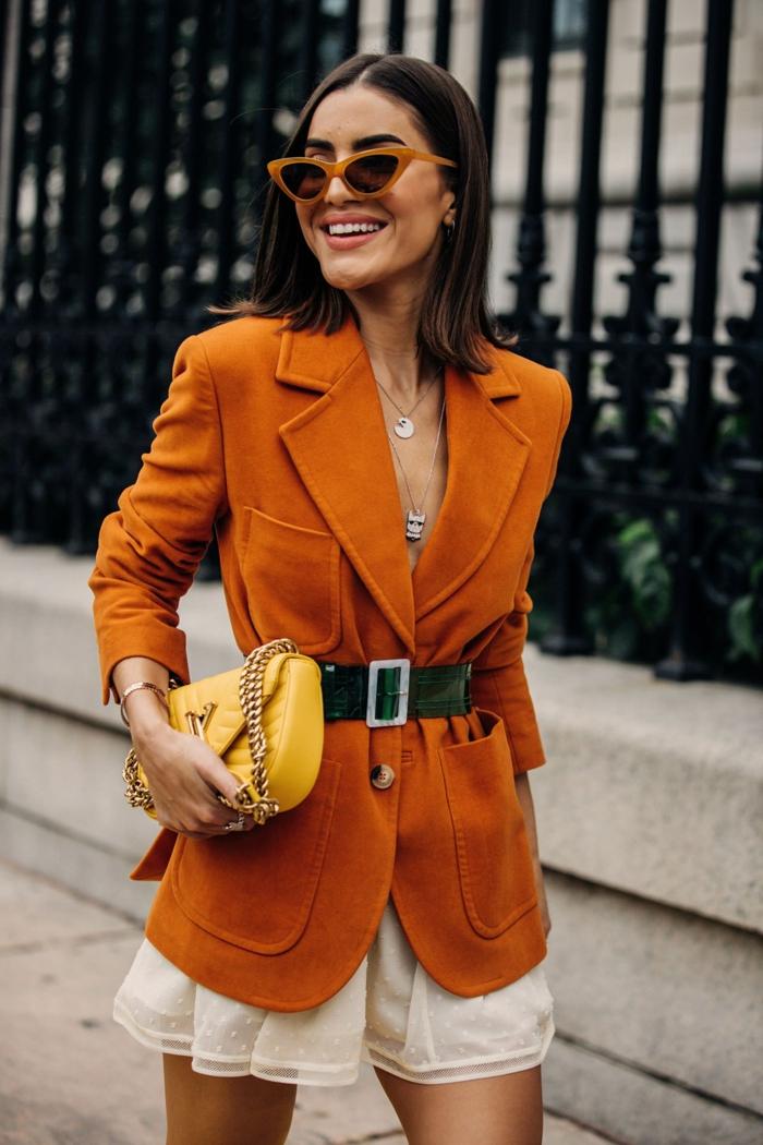 sac bandoulière femme, veste en daim orange, lunettes de soleil cadre orange, jupe mini blanche
