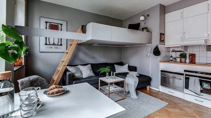 canapé gris et table de salon sous lit en hauteur blanc, murs gris et kitchenette pour studio blanche, table salle à manger blanche
