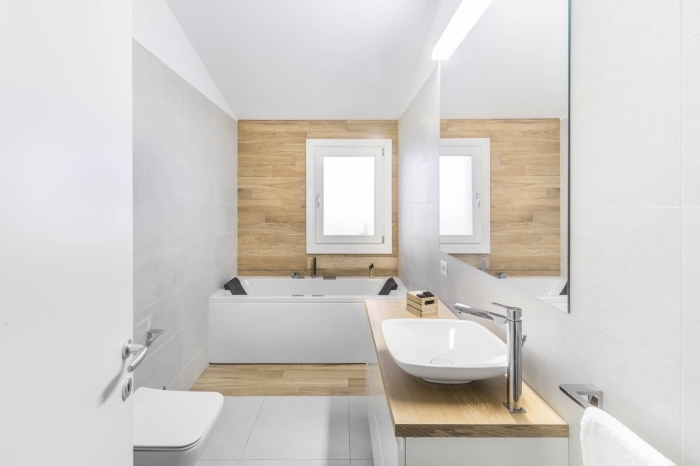 idée salle de bain minimaliste aux murs en carrelage gris clair et peinture blanche avec pan de mur en lambris bois