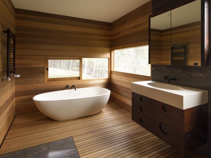 comment aménager une salle de bain rustique aux murs en lambris bois avec baignoire autoportante, modèle carreaux imitation marbre gris