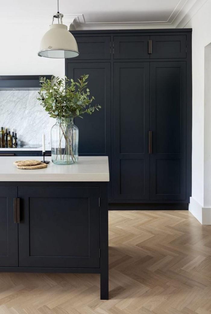 décoration cuisine moderne avec plancher bois et armoires noir mate, plan de travail en blanc, crédence cuisine marbre