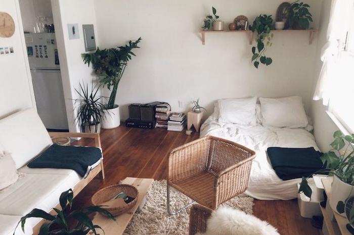 lit matelas au so, adulte cocooning, chaise rotin, canapé bois décoré de coussins blancs, tapis moelleux, étagère surchargée de plantes vertes, style jungle urbaine