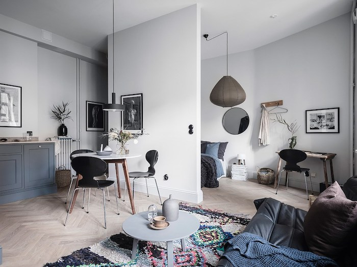 idée comment aménager un studio spacieux avec une chambre à coucher séparée d un mur, coin salon avec canapé cuir noir, table basse ronde, tapis original, table entourée de chaises scandinaves