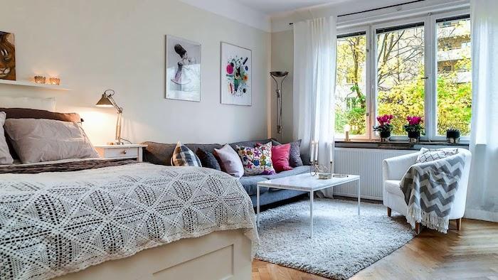 canapé gris et petite table basse blanche design sur tapis gris, fauteuil gris, lit style traditionnel, murs beige clair, cadres décoratifs