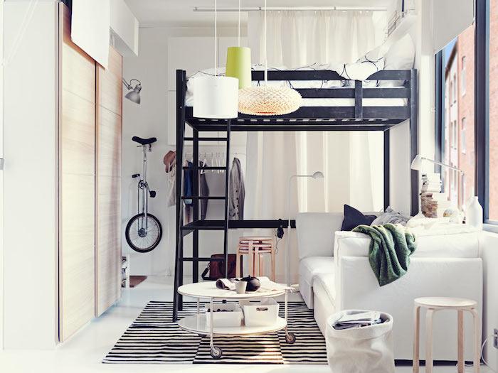 lit en hauteur noir, canapé blanc et table basse ronde à roulettes sur tapis zèbre, murs blancs, rideaux pour voiler une fenêtre, armoire à porte coulissantes bois