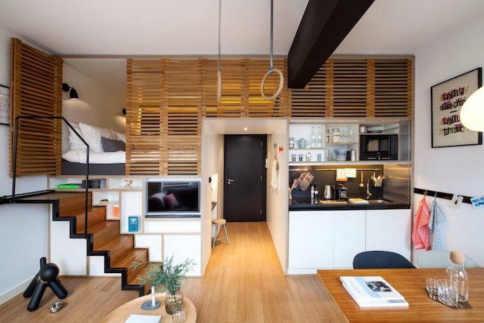 espace nuit chambre à coucher en hauteur mezzanine séparée d une grille de bois, kitchenette miniature, coin salle à manger, architecture moderne