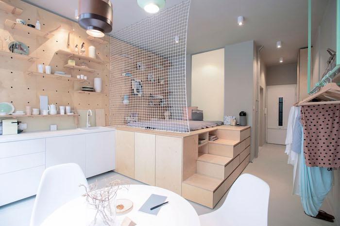 mur perforé derrière une cuisine blanche avec meuble bas, table scandinave ronde entourée de chaises, lit sur estrade en bois, décoration studio
