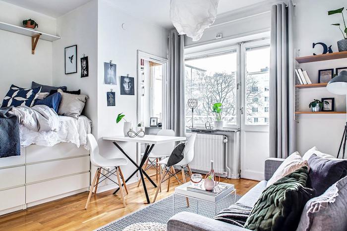 lit hait surchar'ge de linge de lit et coussin décoratifs, table et chaises salle à manger scandinaves, tapis gris, canapé gris décoré de coussins décoratifs, rideaux gris