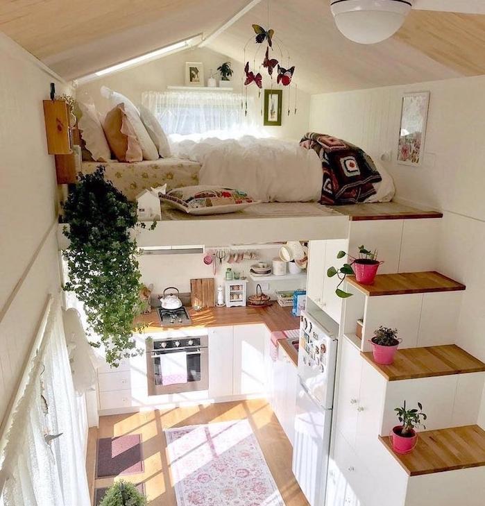 lit sur un deuxième étage auquel mène un escalier un bous, amenagement coin nuit sous pente, cuisine compacte en bois et blanc