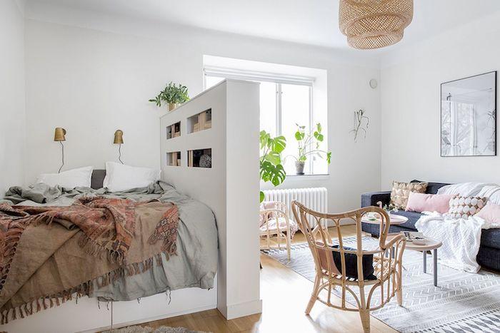 modele deco studio avec lit à linge bohème chic séparé par un pan de mur bibliothèque, niche d un salon avec canapé gris, chaises en rotin, coussins et plaid coloré