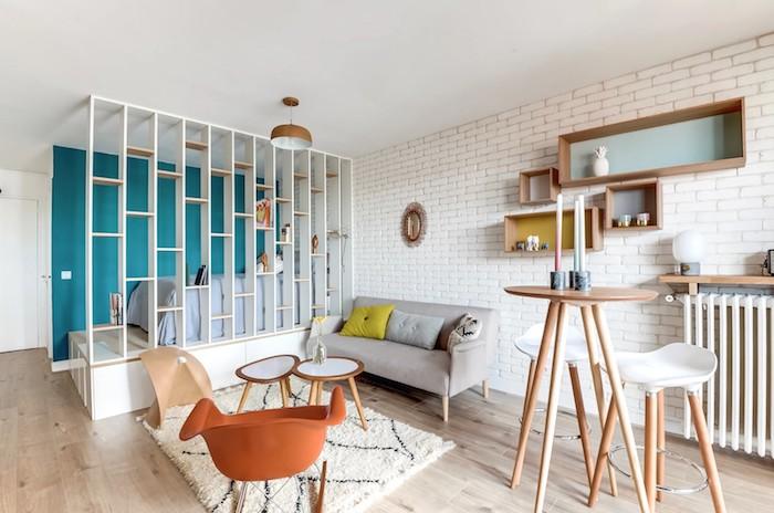 claustra intérieur pour séparer une chambre à coucher d un salon avec canapé gris, tables gigognes et chaise orange à bascule, mur à cagettes de bois rangement, bar tabourets scandinaves et table à pieds hautes