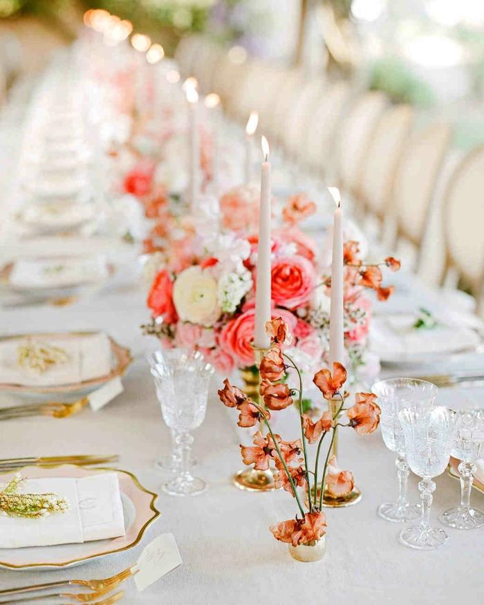 table de mariage blanche, roses magnifiques, bougies allumées blanches, assiettes aux rebords dorés