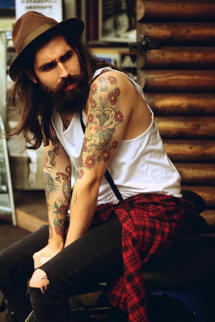 tatouages bras fleurs colorés, débardeur blanc, chapeau marron, chemise carreaux rouge, jean déchiré