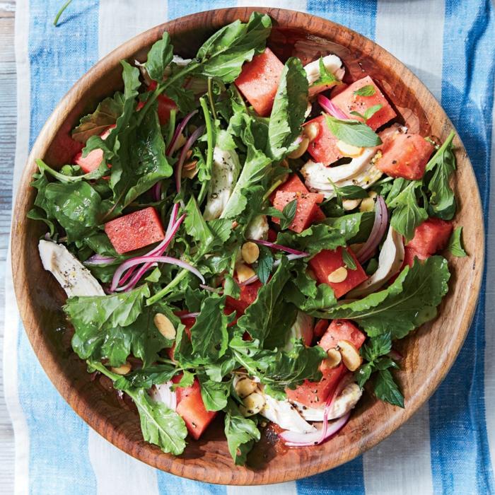 entrée salade servie dans assiette en bois, morceaux de tomates, roquette, oignons, noix de cajou