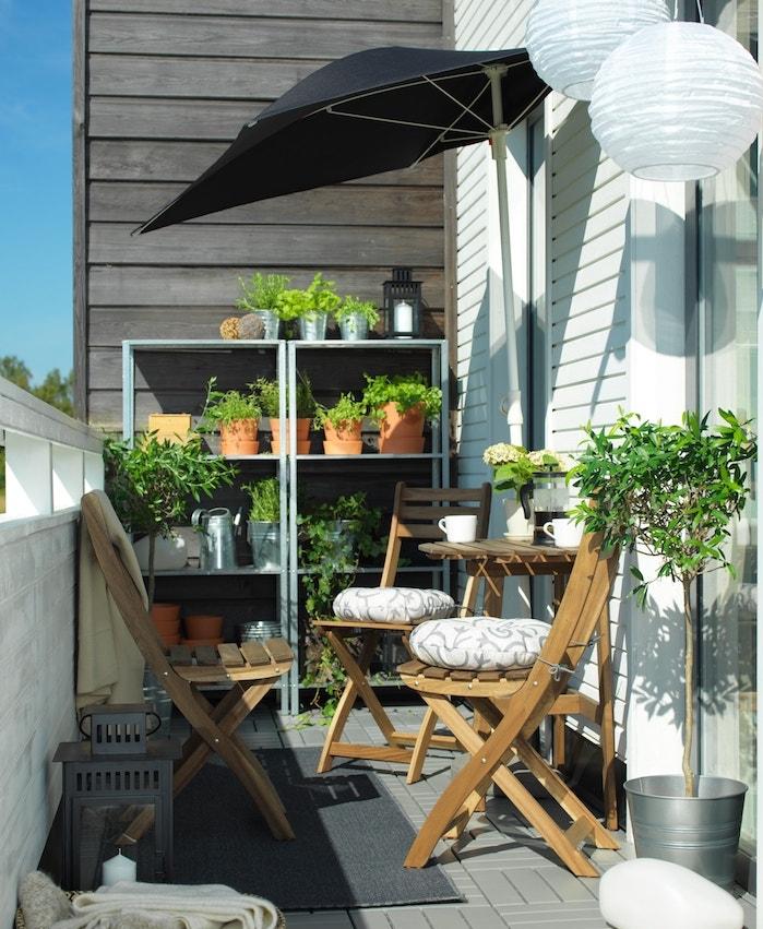 suspensionboule blanche pour décorer un balcon aménagé avec dec haises de bois et parasol de balcon, tapis gris, étagère pots de fleurs