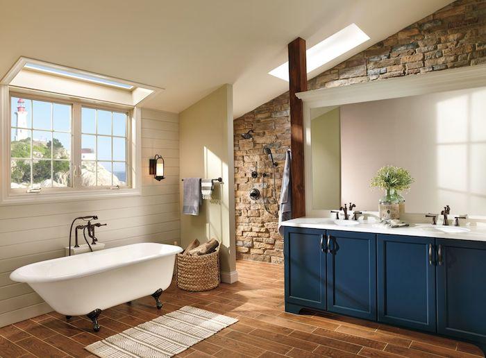 idee salle de bain style campagne chic avec meuble salle de bain bleu nuit et baignoire ancienne sur parquet marron, mur de pierres, lambris blanc