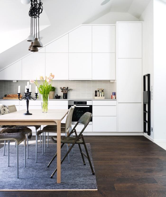 une cuisine mansardée entièrement blanche au design épuré avec système de fermeture sans poignées, ouverte sur une salle à manger, meuble sous pente aménager une cuisine mansardée