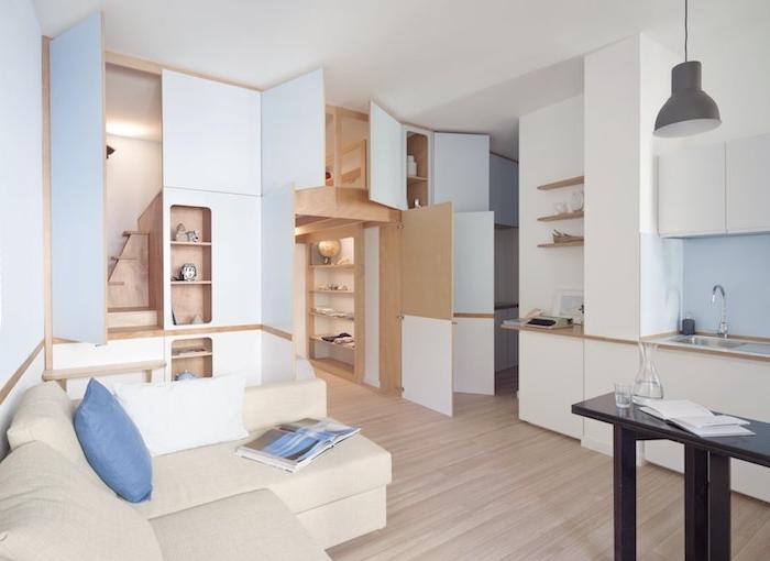 rangement caché à plusieurs étagères dans meuble de bois, canapé d angle beige claire, cuisine classique blanche, idée deco en bois et blanc, design intérieur minimaliste