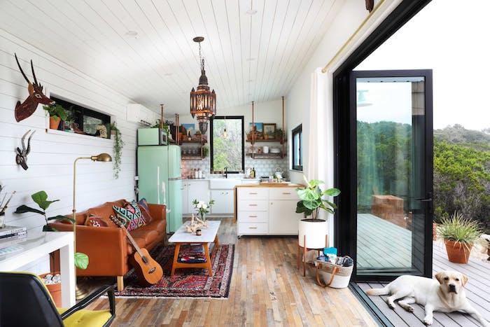 deco style boheme chic dans une cuisine ouverte sur salon avec canapé en cuir marron, tapis oriental, frigo vert, cuisine blanche avec petit ilot, plantes vertes d intérieur