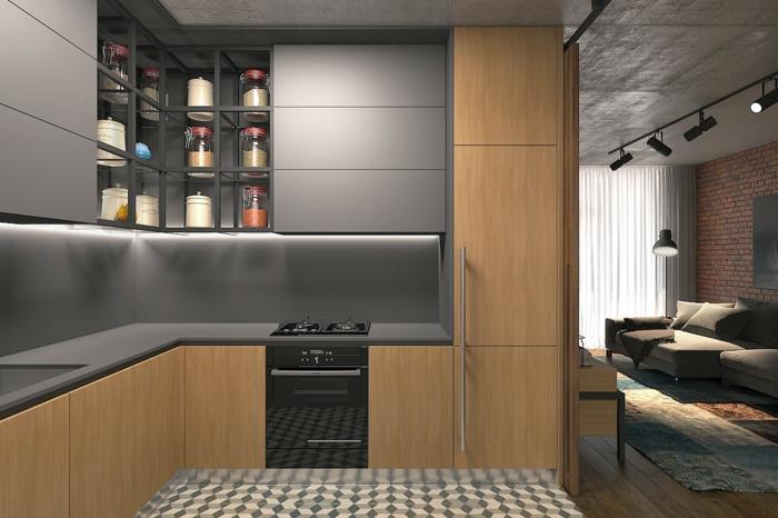 petite cuisine équipée en gris et bois, cuisinière à encastrer, déco sol carreaux de ciment, sofa gris, mur en briques, cuisine et séjour