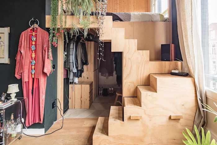 chambre en noir et bois , lit sur estrade mezzanine en bois avec matelas au sol, plantes vertes d interieur deco hippie chic