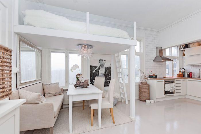 coin salon salle à manger sous lit en hateur blanc, table chaises et canape sur tapis gris clair, kitchenette pour studio blanche
