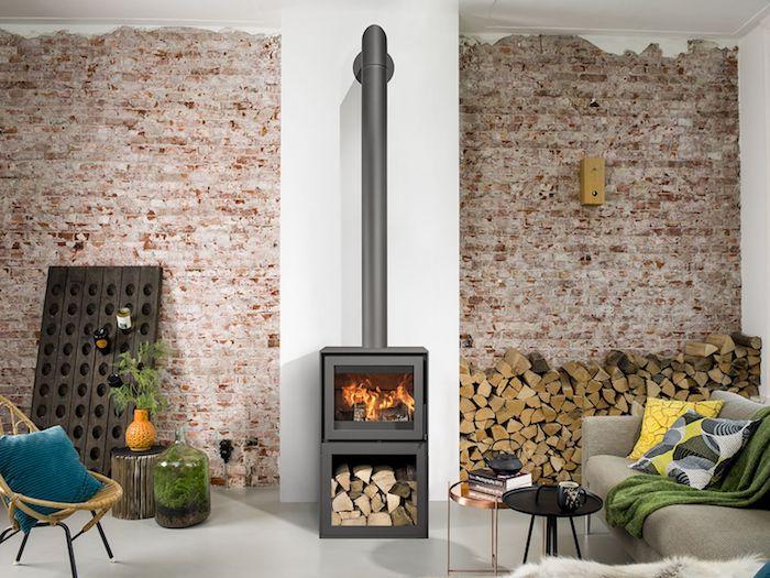 idée de poele a bois dans un salon rustique avec mur de briques, des bûches stockés, canapé gros et coussins colorés, sol gris clair