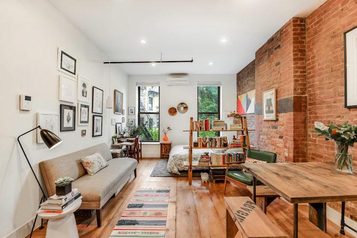 chambre à coucher séparée d un salon, salle à manger avec une bibliothèque en bois, mur de cadres, canapé gris et table et bancs salle à manger en bois