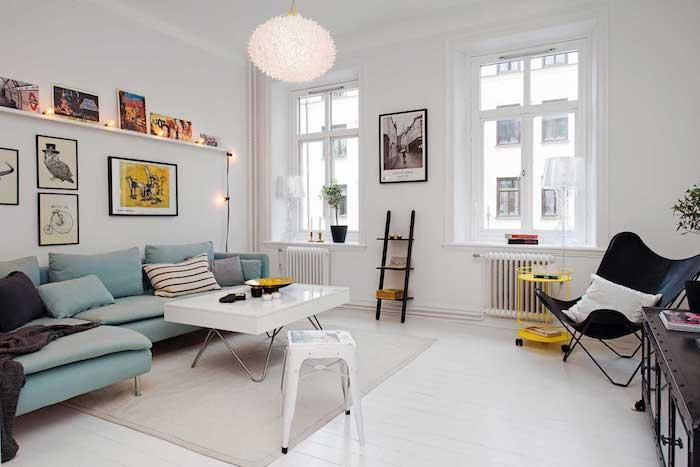 canapé d angle bleu et table blanche pliante à côté, murs blancs et suspension design, eco mur de cadres et guirlande lumineuse pour deco cocooning scandinave