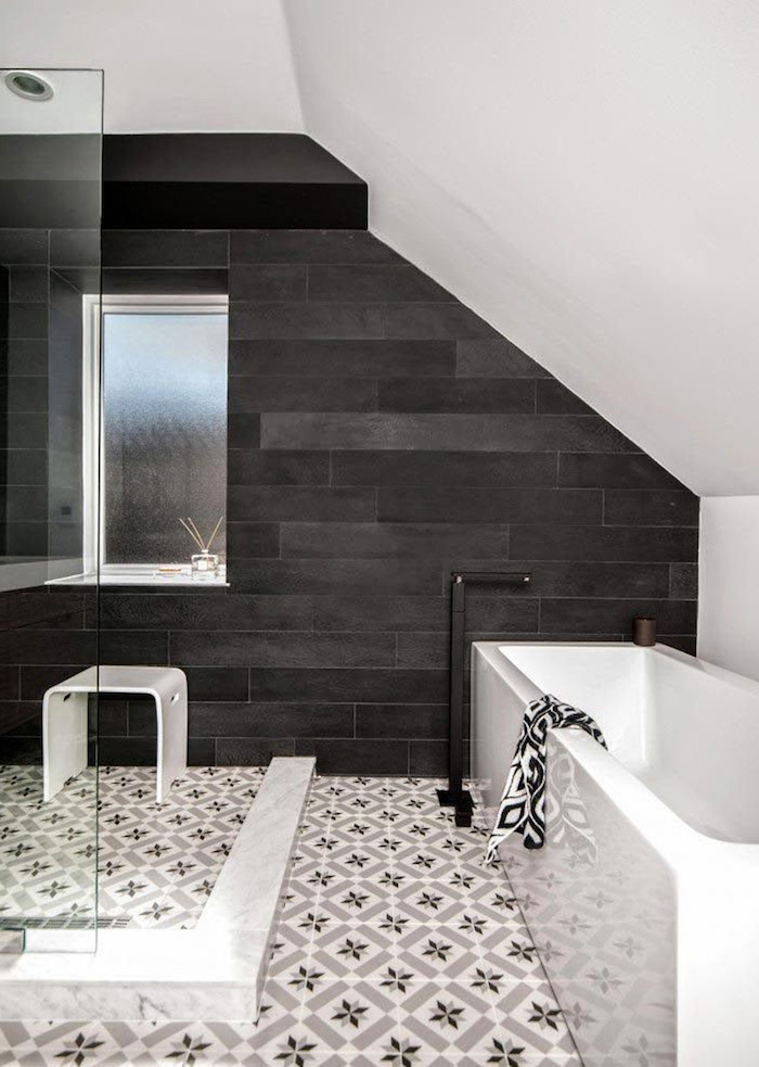 mur d accent gris anthracite dans une salle de bain avec baignoire blanche et carrelage à motifs floraux