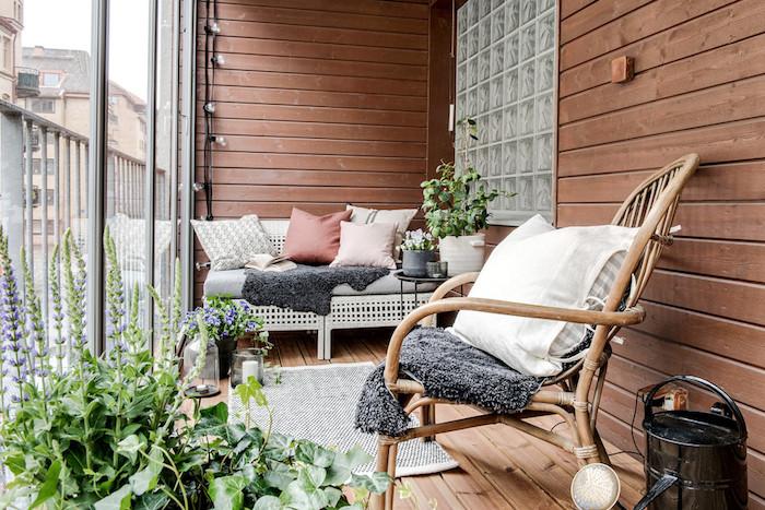 aménager un balcon en longueur avec canapé cocooning avec coussins et plaid gris, chaise de bois design, revetement terrasse en bois, plantes vertes d exterieur
