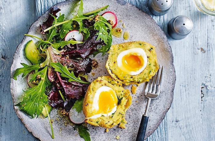 oeufs à l écossaises enveloppées de patates servis avec des salades vertes, idee repas soir rapide et facile