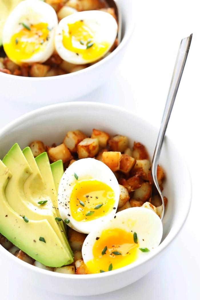 bol de petit déjeuner avec des oeufs mollets, des tranches d'avocat et des patates douces rôties au four