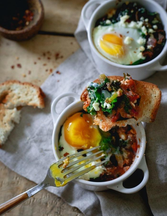 des oeufs cocottes aux épinards et au fromage préparés dans des ramequins à déguster avec des tartines croustillantes, recette rapide pour le soir ou ou le déjeuner