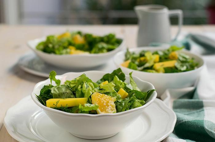 idée salade, laitue, mangue et orange, carafe blanc, trois assiettes remplies de salade verte