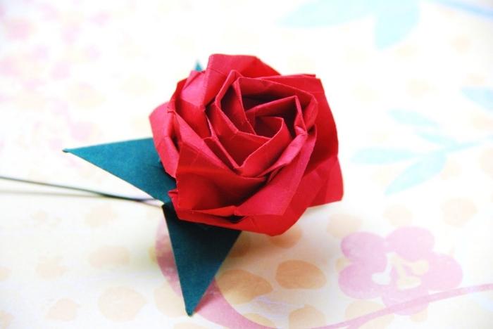 modèle d'origami fleur rose avec ses feuilles vertes en papier, joli pliage de rose délicate en papier