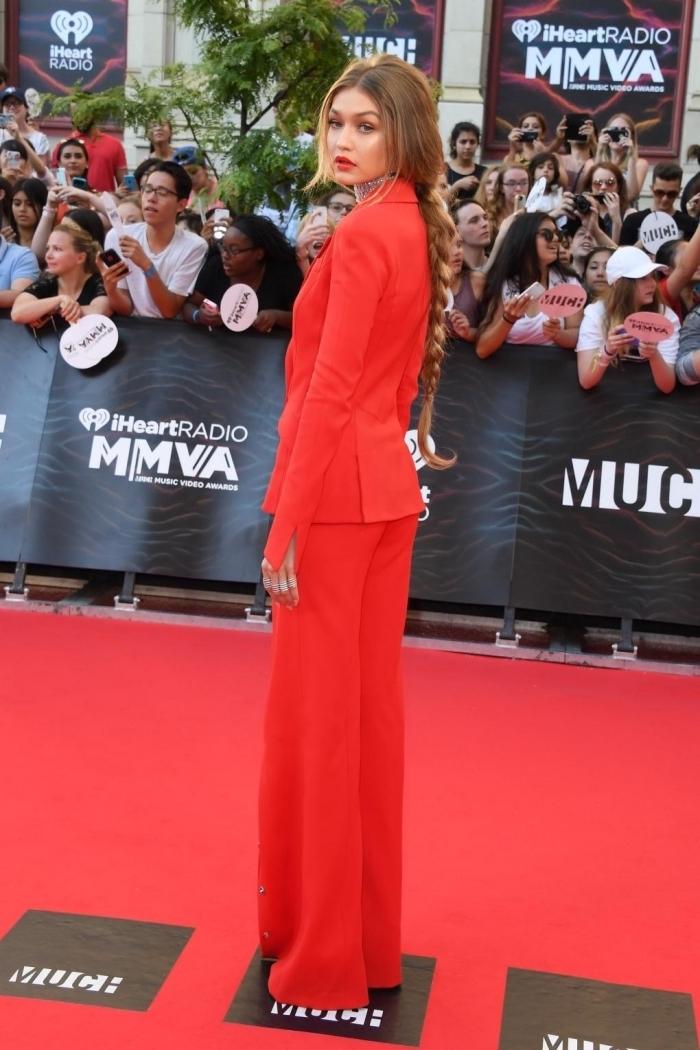 idée coiffure pour cheveux longs avec queue de cheval basse tressée, modèle de costume femme avec pantalon large en rouge