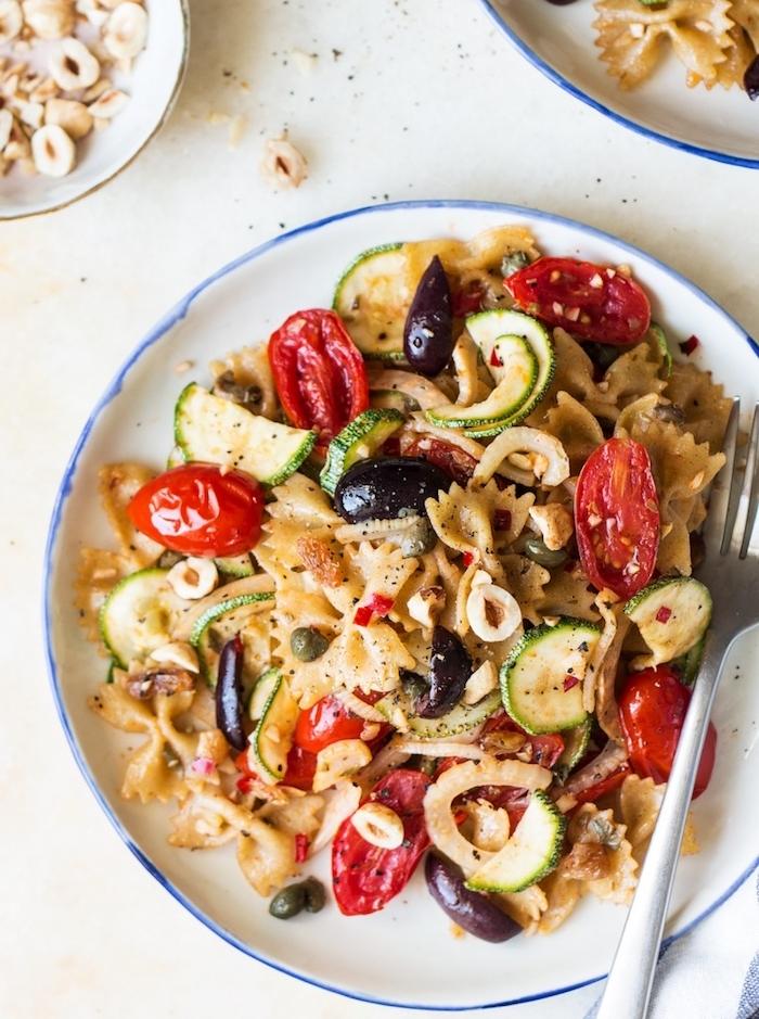 pâtes italiennes aux tomates cerise, olives, courgettes dans une assiette, idée de menu vegetarien repas rapide