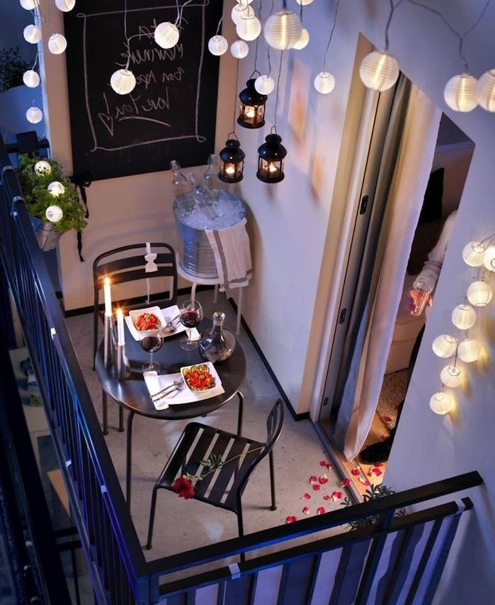 decoration de balcon romantique avec guirlande lumineuse, table et chaises en metal noires, organiser un diner romantique, lanternes suspendues, guirlande boule lumineuse pour ambiance cosy