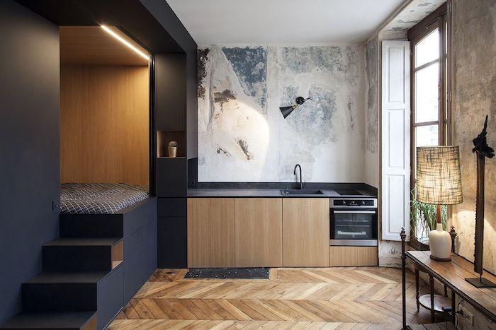 aménagement studio 20 m2 avec cuisine noire et bois et coin chambre à coucher sur estrade niche noire, parquet bois clair