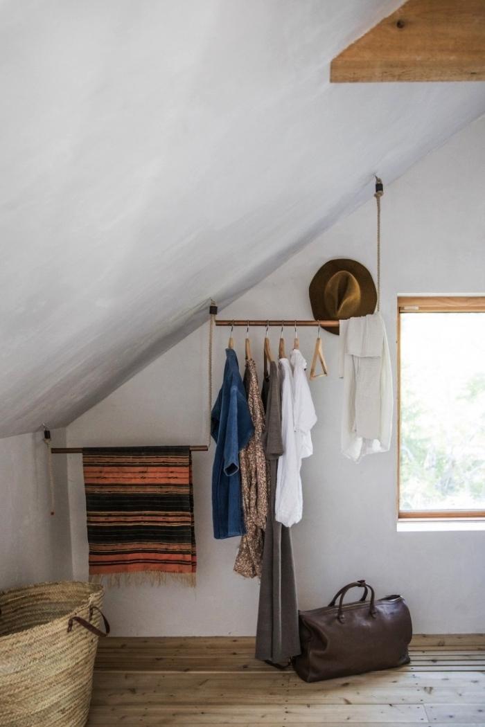 une penderie sous pente aménagée dans un coin de la chambre mansardée avec des barres fixées au mur