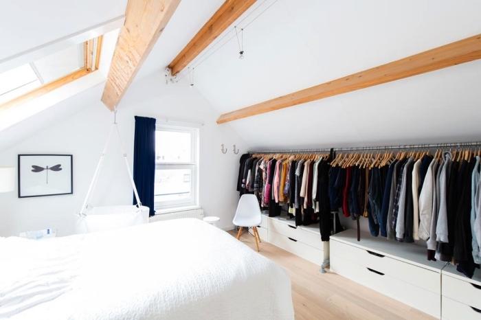 une chambre à coucher mansardée de style scandinave minimaliste avec dressing sous pente ouvert qui suit la pente du toit