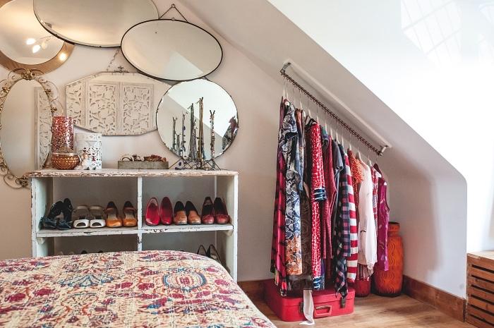 une penderie sous pente minimaliste aménagée dans un coin de la chambre à coucher bohème chic avec barre fixée sur le mur