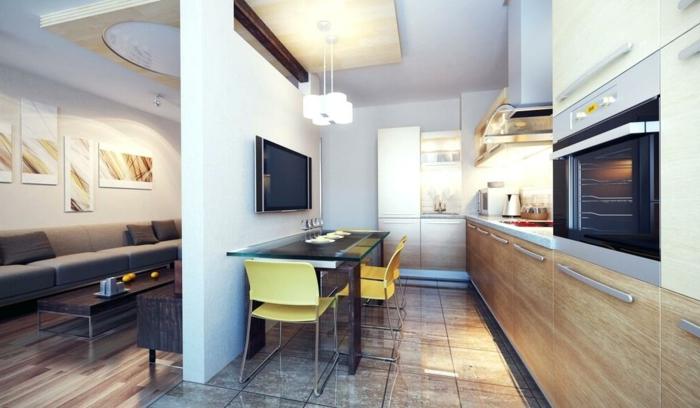 comment aménager petit studio avec cuisine, table longue noire, chaises jaunes, mur de séparation et séjour moderne