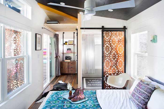 interieur deco boheme chic avec lit boheme à linge coloré, espace salon séparé de porte coulissante, parquet bois brut, meuble industriel vintage