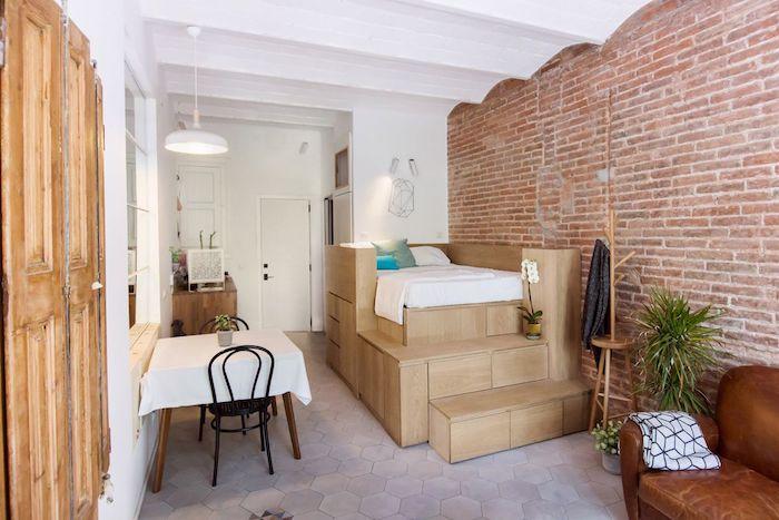 lit sur estrade en bois à coté d un mur de briques, coin repas et canapé en cuir design, aménagement studio 25 m2